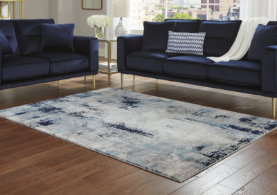 Room picture of R404871 Leonelle Rug With a cream hue and shades of blue and gray, it complements a variety of interior design themes.